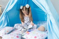 Enfant jouant avec une tente de tipi Photos stock