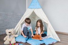 Enfant jouant avec une tente de tipi Image stock