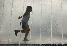 Enfant jouant dans la fontaine d'eau Images libres de droits