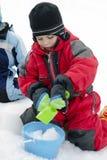 Enfant jouant dans la neige Photos stock
