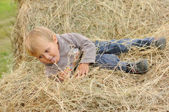 Enfant jouant dans la pile de foin Photographie stock libre de droits