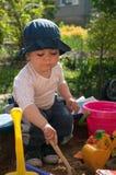 Enfant jouant dans le bac à sable Photos stock