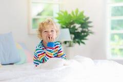Enfant jouant dans le lit Badine la pièce Bébé garçon à la maison images libres de droits
