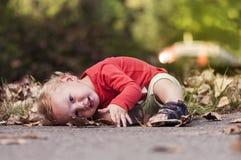 Enfant jouant dans les feuilles Photographie stock