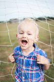 Enfant jouant dans un filet du football Photographie stock libre de droits