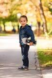 Enfant jouant dehors avec la planche à roulettes Photos stock