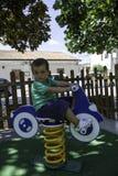 Enfant jouant dehors sur le carrousel Photos stock