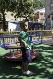 Enfant jouant dehors sur le carrousel Photos libres de droits