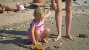 Enfant jouant en sable fille caucasienne heureuse de plage à la petite, enfant ayant l'amusement avec Sandy Toys clips vidéos