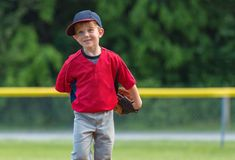 Enfant jouant heureusement au base-ball image stock