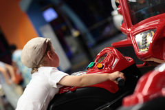Enfant jouant la machine de simulateur d'arcade Photographie stock libre de droits