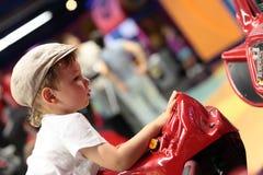 Enfant jouant la machine de simulateur d'arcade Images stock