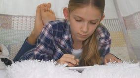 Enfant jouant la Tablette dans la fille de salle de jeux écrivant des devoirs pour le terrain de jeu d'enfant d'école images stock