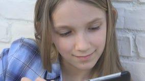 Enfant jouant la Tablette, enfant Smartphone, messages de lecture de fille passant en revue l'Internet clips vidéos