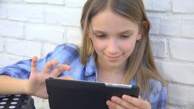 Enfant jouant la Tablette, enfant Smartphone, messages de lecture de fille passant en revue l'Internet photos libres de droits