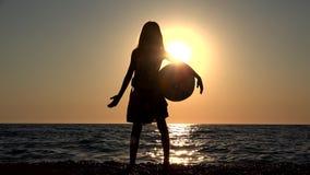 Enfant jouant le ballon de plage dans le coucher du soleil, vagues de observation de mer d'enfant, vue de fille au crépuscule banque de vidéos