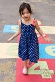 Enfant jouant le jeu de marelle/enfant jouant le jeu de marelle sur le terrain de jeu Image libre de droits