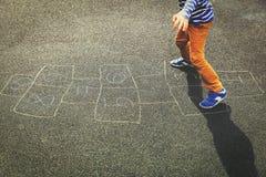 Enfant jouant le jeu de marelle sur le terrain de jeu Photographie stock libre de droits