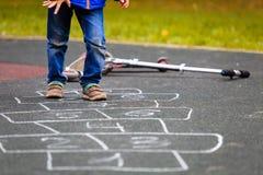 Enfant jouant le jeu de marelle sur le terrain de jeu dehors Images libres de droits