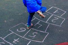 Enfant jouant le jeu de marelle sur le terrain de jeu dehors Image stock