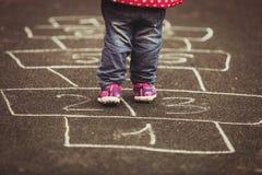 Enfant jouant le jeu de marelle sur le terrain de jeu dehors Photos stock