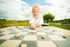 Enfant jouant les ébauches ou le jeu de société de contrôleurs extérieur image libre de droits