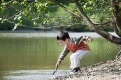 Enfant jouant par le lac Photographie stock