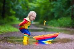 Enfant jouant sous la pluie Photos libres de droits