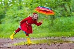Enfant jouant sous la pluie Photo stock