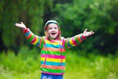 Enfant jouant sous la pluie Photographie stock libre de droits