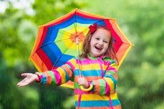 Enfant jouant sous la pluie Image libre de droits