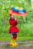 Enfant jouant sous la pluie Photographie stock