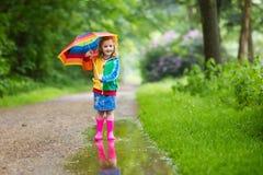 Enfant jouant sous la pluie avec le parapluie Photos libres de droits