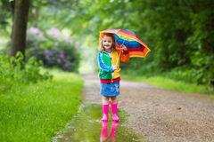 Enfant jouant sous la pluie avec le parapluie Photographie stock libre de droits