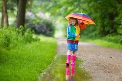Enfant jouant sous la pluie avec le parapluie Photo libre de droits