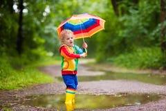 Enfant jouant sous la pluie sous le parapluie Image stock