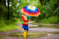Enfant jouant sous la pluie sous le parapluie Photographie stock libre de droits