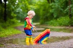 Enfant jouant sous la pluie sous le parapluie Photographie stock