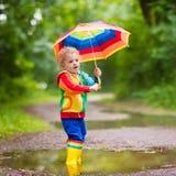Enfant jouant sous la pluie sous le parapluie Photos stock