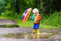 Enfant jouant sous la pluie sous le parapluie Images stock