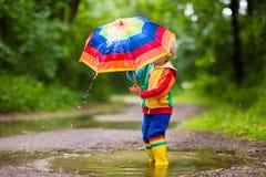 Enfant jouant sous la pluie sous le parapluie Photo libre de droits
