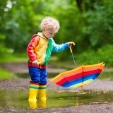 Enfant jouant sous la pluie sous le parapluie Images libres de droits