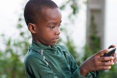 Enfant jouant sur l'extérieur de téléphone dans le jour ensoleillé images stock