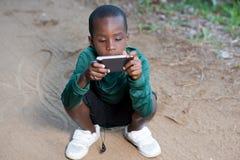 Enfant jouant sur l'ext?rieur de t?l?phone dans le jour ensoleill? images stock