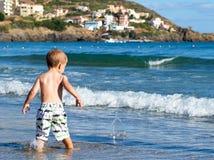 Enfant jouant sur la plage Photo stock