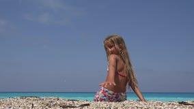 Enfant jouant sur la plage dans le coucher du soleil, cailloux de lancement de sourire de fille en eau de mer banque de vidéos