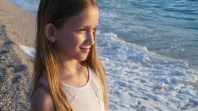 Enfant jouant sur la plage dans le coucher du soleil, vagues de observation de mer d'enfant, portrait de fille sur le rivage banque de vidéos