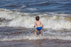 Enfant jouant sur une plage images libres de droits