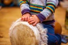 Enfant jouant un tambour de djembe avec les configurations naturelles de fourrure de chèvre image stock