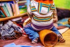 Enfant jouant un tambour de djembe avec les configurations naturelles de fourrure de chèvre images libres de droits